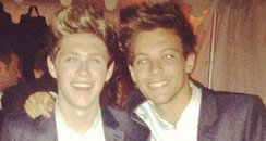 Niall Horan and Louis Tomlinson wearing the same su