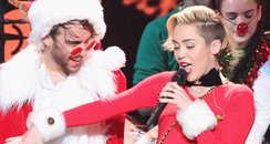 Miley Cyrus on stage with santa
